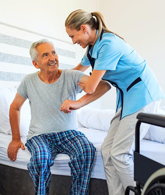 caregiver assisting senior man to stand up