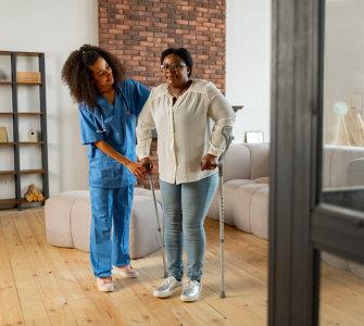 caregiver assisting senior woman walking