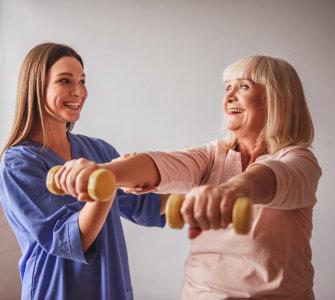 caregiver assisting senior woman exercising