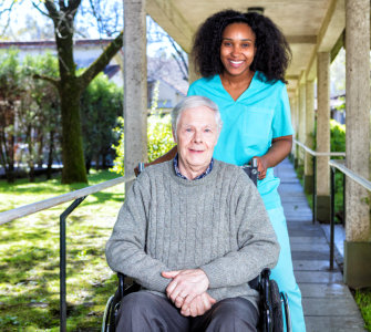 caregiver and senior woman sitting in the wheelchair smiling