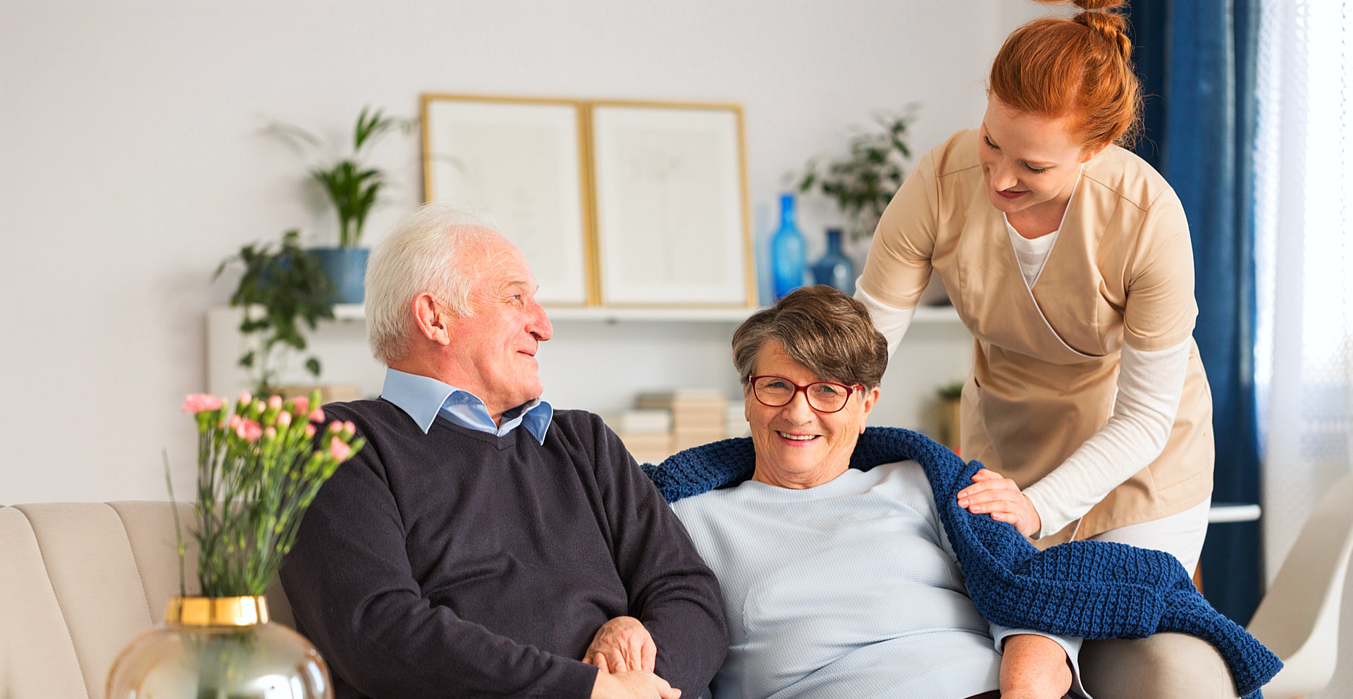 caregiver give blanket to senior woman while senior man looking at the caregiver