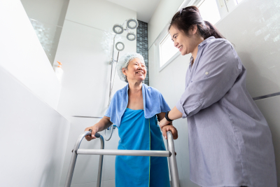 caregiver assisting a senior woman taking a shower