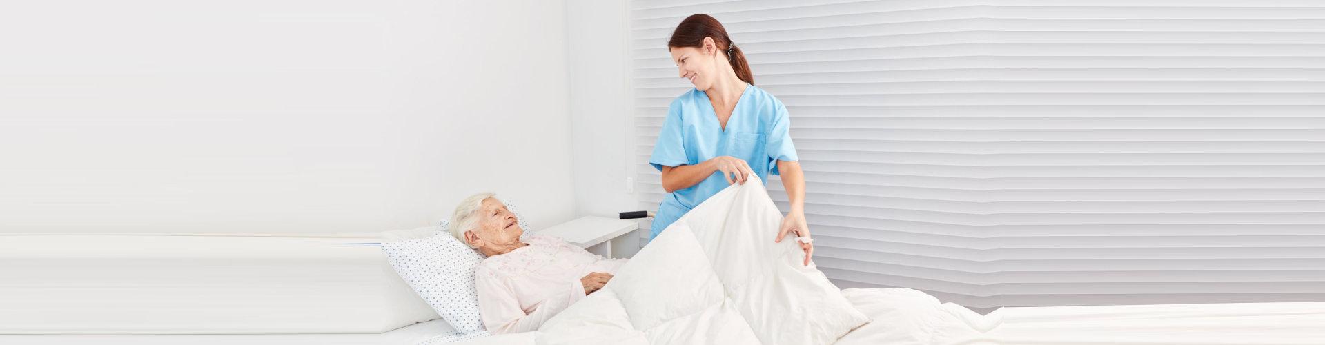 nurse taking care of a sick senior citizen in bed